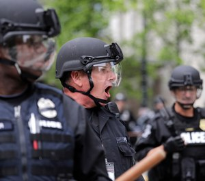 A Seattle police officer yells out orders at Seattle City Hall as protesters march toward them Wednesday, June 3, 2020, in Seattle. (Photo/AP)