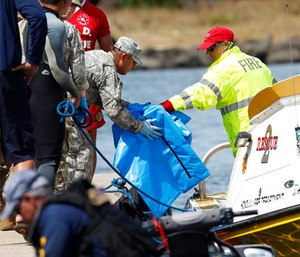 Water safety officials hand over possible debris from an Army UH-60 Black Hawk helicopter crash to military personnel stationed at a command center in a harbor.