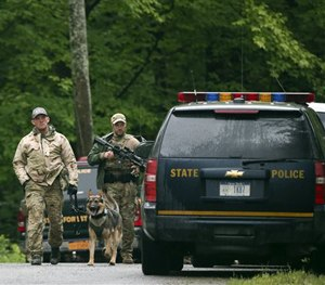 Law enforcement officers walk along a road on Sunday, June 28, 2015. (AP Image)