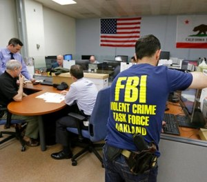 In this Friday, March 10, 2017, photo, Oakland police detectives and FBI agents work together in the offices of the Oakland Safe Streets Task Force in Oakland, Calif.