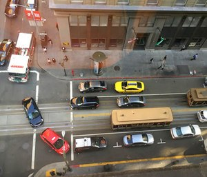 A fire truck at top left and other traffic try to make their way around a pair of idled cablecars on California Street after a large power outage.