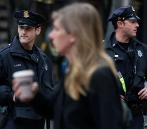 Police officers Alan Katz (left) and Chris Simpson patrol on foot at Powell and Market streets in San Francisco, Calif.