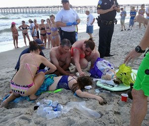 Emergency responders help a teenage girl following a shark attack in Oak Island, North Carolina.