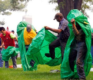 Volunteers learn to deploy fire shelters with practice equipment after a call out by fire officials seeking to supplement their usual resources in Omak, Wash.