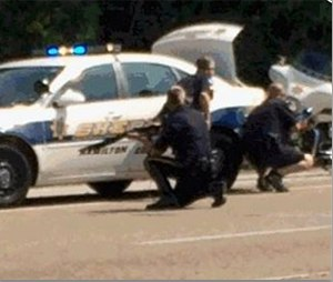 In this image made from video and released by WRCB-TV, authorities work an active shooting scene on amincola highway near the Naval Reserve Center, in Chattanooga, Tenn. on Thursday, July 16, 2015. (WRCB-TV via AP)