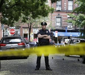 A police officer stands near a crime scene on Monday, July 28, 2014 in New York. Authorities say a sex-assault suspect got in a shootout with law enforcement in New York City that wounded the suspect, two federal marshals and a police officer. (AP Image)