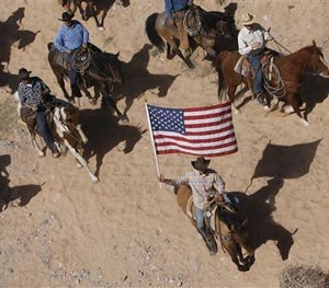 In this April 12, 2014, file photo, the Bundy family and their supporters fly the American flag as their cattle is released by the Bureau of Land Management back onto public land outside of Bunkerville, Nev. (AP Image)