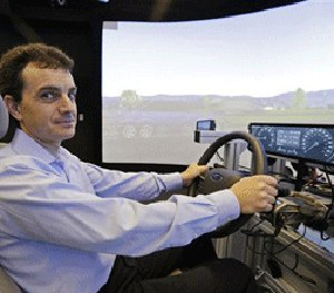 Technical director Dragos Maciuca poses while sitting in a driving simulator in the immersion lab of the Ford Motor Company Research and Innovation Center in Palo Alto, Calif.