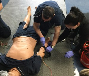 Paramedic students at Delaware Technical Community college practice hemorrhage control in a lab scenario.