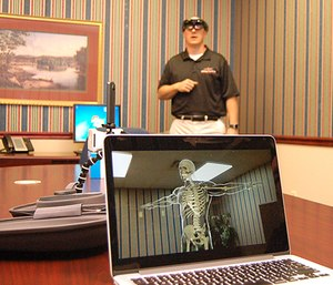 A holographic image of a human skeleton appears on a laptop computer while it's being controlled by David Blevins, in background, director of EMS programs at Roane State Community College. (Photo/Roane State University)