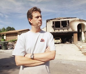 Scott Miller, the LAFD firefighter who got shot in the face during the 1992 riots, stands outside his fire-damaged home, May 17, 1996 in Newbury Park, Calif. (AP Photo/Nick Ut)
