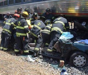 Emergency officials respond after a train and car crashed in Indianapolis.