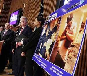 In this April 12, 2013 photo, NYPD officials stand next to photos that accused cocaine dealers posted on social media. The suspects posed with stacks of cash, guns and diamond-crusted watches.