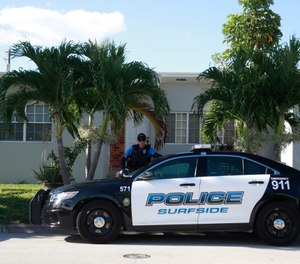 A town of Surfside, Fla., police officer stands guard in front of the home of Sol Pais, Wednesday, April 17, 2019, in Surfside, Fla. (AP Photo/Wilfredo Lee)