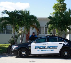 A town of Surfside, Fla., police officer stands guard in front of the home of Sol Pais, Wednesday, April 17, 2019, in Surfside, Fla.