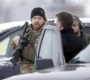 Members of the FBI stand guard at the Burns Municipal Airport, Sunday, Jan. 10, 2016, in Burns, Ore.