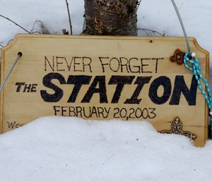 A wooden placard rests in the snow at the site of the Station nightclub fire, Wednesday, Feb. 20, 2013, in West Warwick, R.I. (AP Photo/Steven Senne)