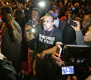 Crowds confront police near the scene in in south St. Louis where a man was fatally shot by an off-duty St. Louis police officer on Wednesday, Oct. 8, 2014.