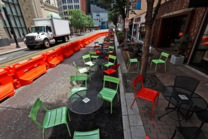 Orange barriers enclose chairs and tables that will be used for dining along Sixth Street between Liberty and Penn avenues in downtown Pittsburgh. Many local governments are offering creative solutions to get businesses back up and running as soon as possible. Image: AP Photo/Gene J. Puskar