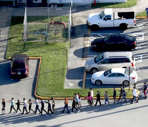 Students are evacuated by police from Marjory Stoneman Douglas High School in Parkland, Fla.