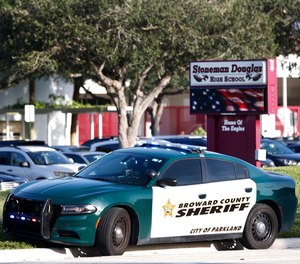 In an Aug. 15, 2018 file photo, a Broward County Sheriff's Office vehicle is parked outside Marjory Stoneman Douglas High School, in Parkland, Fla.