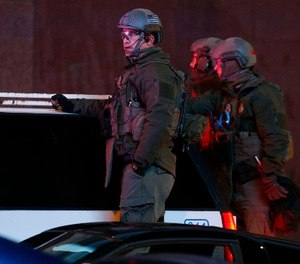 Denver Police Department SWAT team members survey Denver Broncos fans as they celebrate the team's victory over the Carolina Panthers in Super Bowl 50 near intersection of 15th and Champa Street late Sunday, Feb. 7, 2016, in Denver. (AP Photo/David Zalubowski)