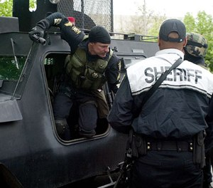Whitman County Sheriff Deputy Chris Chapman climbs out of the Whitman County Washington Regional SWAT Team armored vehicle outside the Moscow Police Department in Moscow, Idaho, Sunday, May 20, 2007.