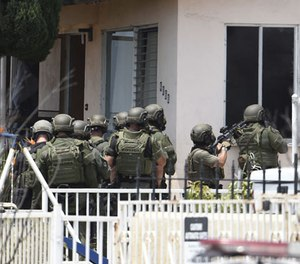 San Diego Police SWAT officers break out windows as they enter a house with a possible suspect inside Friday, July 29, 2016 in San Diego. (AP Photo/Denis Poroy)