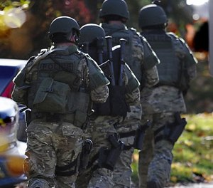 SWAT move in a line on the campus of Central Connecticut State University, Monday, Nov. 4, 2013, in New Britain, Conn.