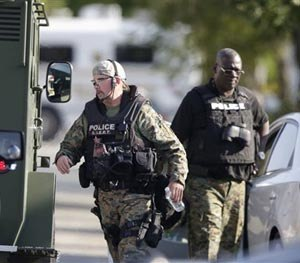 Police don body armor as authorities negotiate with two men who are barricaded in a home and holding a woman and five children hostage in the south suburb of Harvey, Ill., Tuesday, Aug. 19, 2014, south of Chicago. (AP Image)
