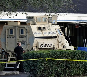 A Sebring, Fla., police officer stands near a Highlands County Sheriff's SWAT vehicle that is stationed in front of a SunTrust Bank branch, Wednesday, Jan. 23, 2019, in Sebring, Fla. (AP Photo/Chris O'Meara)