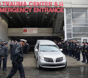 Police officers salute as the hearse carrying the body of Philadelphia police officer Cpl. James O'Çonnor leaves the hospital in Philadelphia, Pa. (Photo/TNS)