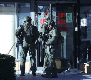 Police officers in SWAT gear enter a pawn shop Thursday, Oct. 5, 2017, in Roswell, Ga., as they search for a burglary suspect. (AP Photo/John Bazemore)
