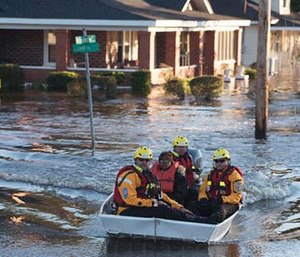 A swift water rescue team transports a resident of to safety on a street covered with floodwaters caused by rain from Hurricane Matthew in Lumberton, N.C. (AP Photo/Mike Spencer)