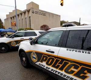 Pittsburgh Police vehicles close the street adjacent to the Tree of Life Synagogue on Saturday, Nov. 3, 2018, before a Shabbat morning service is held on the street corner in the Squirrel Hill neighborhood of Pittsburgh. (AP Photo/Gene J. Puskar)