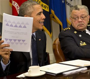 Philadelphia Police Commissioner Charles Ramsey watches as President Obama holds up a copy of the interim report of the President's Task Force on 21st Century Policing, Monday, March 2, 2015.