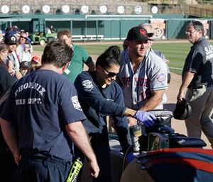 Scottsdale Scorpions outfielder Tim Tebow, center, comforts a fan, on ground, who was suffering a seizure, following Tebow's debut against the Glendale Desert Dogs in a baseball game Tuesday, Oct. 11, 2016, during the Arizona Fall League in Glendale, Ariz.