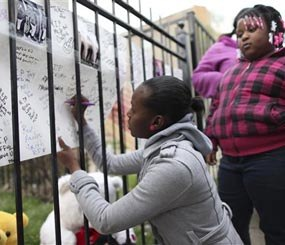 In this April 30, 2014 photo, family and friends of 14-year-old Endia Martin sign posters at a makeshift memorial during a vigil for the girl who was shot and killed April 28 in Chicago allegedly by another 14-year-old girl in a dispute concerning a boy.