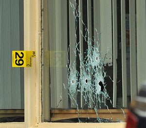 Bullet holes show in a window of a Days Inn Hotel office from a shooting early Thursday morning, July 7, 2016.