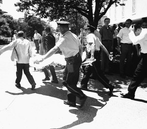 In this Aug. 1, 1966, file photo, one of the victims of Charles Whitman, the sniper who gunned down victims from a perch in the University of Texas tower, is carried across the campus to a waiting ambulance in Austin.
