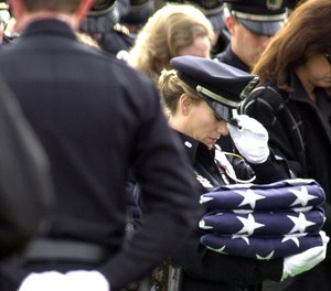 Police honor guard member Naya Pope bows her head while holding three folded American flags for intended for the family of slain Irving, Texas, police officer Aubrey Hawkins during burial services in Irving, Thursday, Dec. 28, 2000.