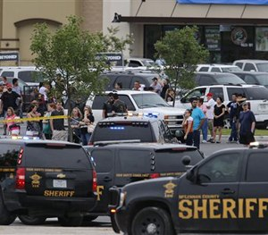 People at the Central Texas MarketPlace watch a crime scene near the parking lot of a Twin Peaks restaurant Sunday, May 17, 2015.