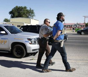 Protester Wyatt Winn is led away in handcuffs outside Big Daddy Zane's bar Monday, May 4, 2020, near Odessa, Texas. Winn was one of several people who showed up to support the bar's owner in her decision to open and serve customers.