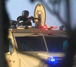 A Hidalgo County Sheriff points a rifle from the top of an armored vehicle Tuesday during a standoff with a capitol murder suspect in La Joya, Texas on Tuesday, July 22, 2014. (AP Image)