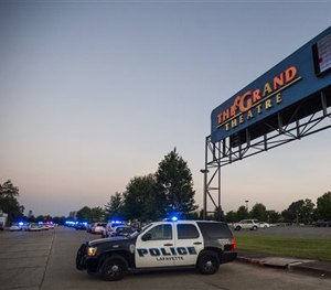 A Lafayette Police Department vehicle blocks an entrance at The Grand Theatre in Lafayette, La., following a shooting at the theater, Thursday, July 23, 2015. (Paul Kieu/The Daily Advertiser via AP)