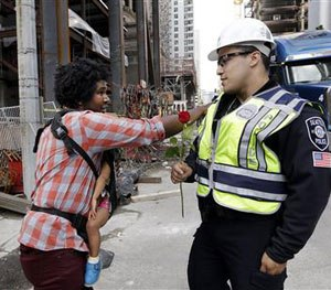 Jasen Frelot, left, holding his daughter Ruby, gives a pat to Seattle police officer Daniel Aguirre after handing the officer a rose in response to the shootings of police officers in Dallas, Friday, July 8, 2016, in Seattle. (AP Image)