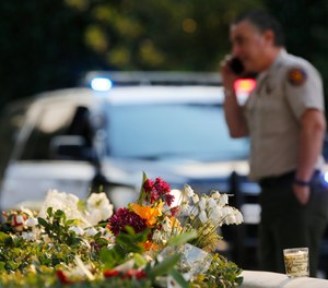 A bouquet of flowers, left by mourners, lays near the site of Wednesday's mass shooting, in Thousand Oaks, Calif., Friday, Nov. 9, 2018. (AP Photo/Damian Dovarganes)
