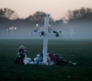 In this Feb. 17, 2018, file photo, an early morning fog rises where 17 memorial crosses were placed, for the 17 deceased students and faculty from the shooting at Marjory Stoneman Douglas High School in Parkland, Fla.