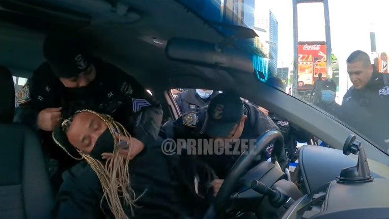 In this screenshot of a YouTube video by Princezee,NYPD officers check the vitals of a man pretending to be unconscious in Times Square in New York, N.Y.