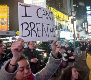 Protesters in Times Square carry signs in reaction to a non indictment against a police officer in the death of Eric Garner, Wednesday Dec. 3, 2014 in New York.